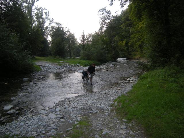 Kolem silnice nenacházíme místo na spaní a volíme variantu brod. Stan schováme za stromy na druhé straně řeky.
